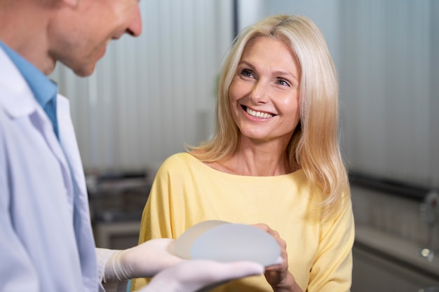 Close up smiley woman holding breast implant