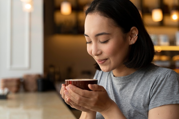 Close up smiley woman holding coffee cup