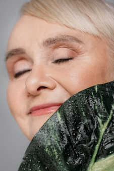 Close-up smiley woman holding leaf
