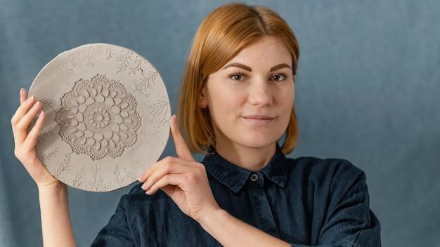 Крупным планом смайлик женщина, держащая тарелку