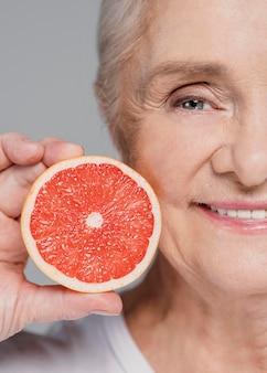 Donna di smiley del primo piano che tiene arancia rossa