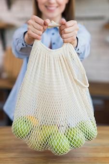 Крупным планом смайлик женщина, держащая многоразовую сумку с фруктами