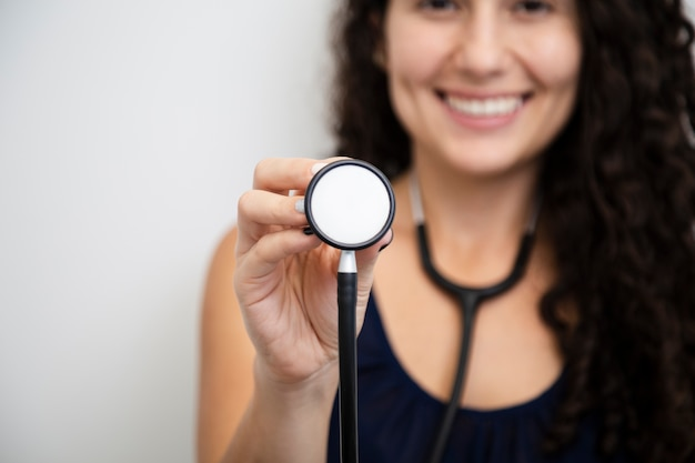 Close-up smiley woman holding a stethoscope
