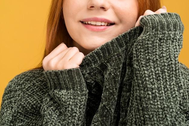 セーターのクローズアップのスマイリー女性