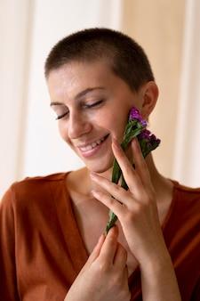 꽃과 함께 포즈를 취하는 웃는 여자를 닫습니다