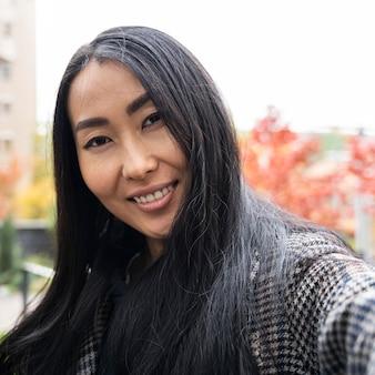 Donna di smiley del primo piano che prende selfie