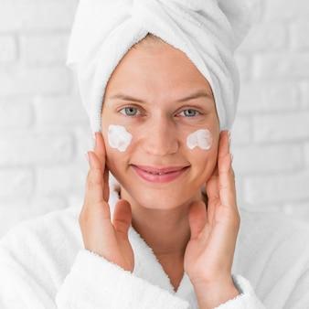Donna di smiley primo piano utilizzando crema per il viso