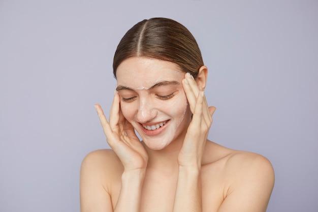 Close up smiley woman using facial mask