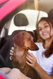 車の中でかわいい犬と笑顔の女性をクローズアップ