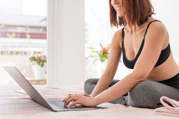 침대에서 노트북으로 근접 웃는 여자