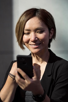 Close up smiley woman with smartphone