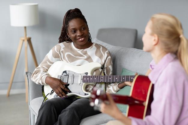 Donne sorridenti ravvicinate che suonano la chitarra a casa