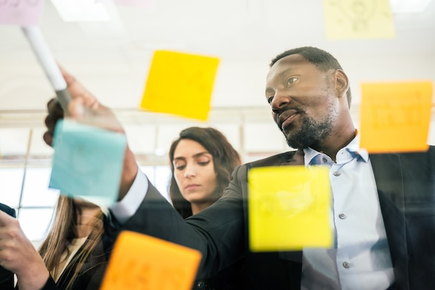 Close-up of smiling african businessman brainstorm meeting with colleagues by using colorful sticky paper note on glass wall for finding new ideas.