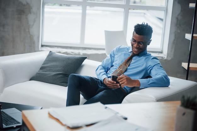 Закройте улыбающийся афроамериканский парень сидит на диване и смотрит на свой смартфон