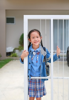집 문 울타리에서 유치원 유니폼을 입은 웃는 아시아 소녀를 닫습니다