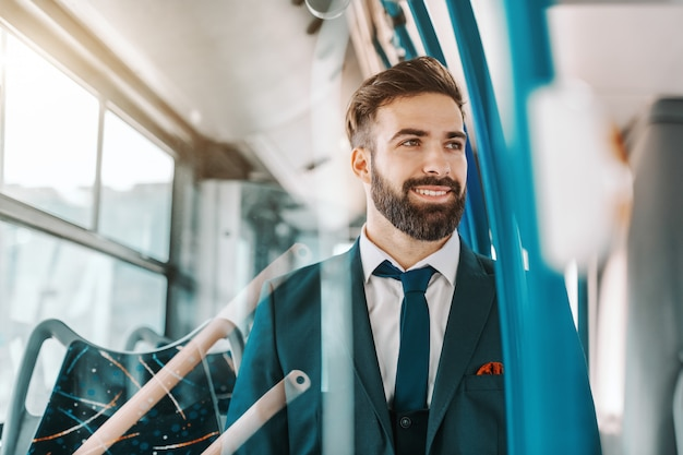 Close up of smiling bearded businessman in formal wear sitting in public transportation and looking through window.