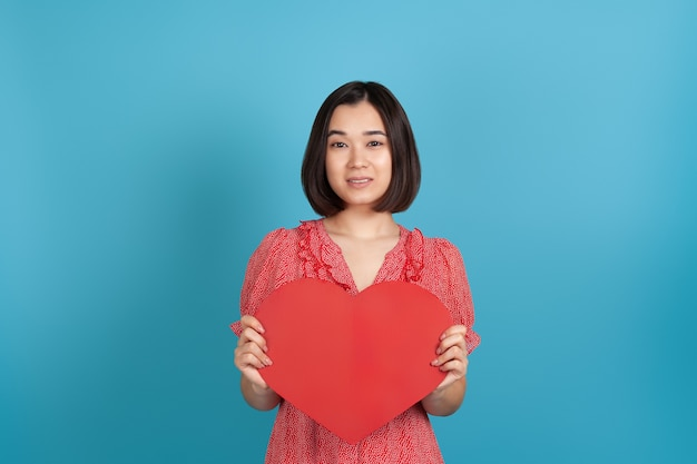 Close-up smiling beautiful young asian woman in a red dress holding a large red paper heart