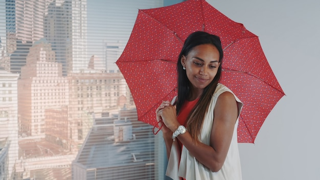 Close-up of smiling black model posing with red umbrella on bar high chair for fashion magazine photo shoot
