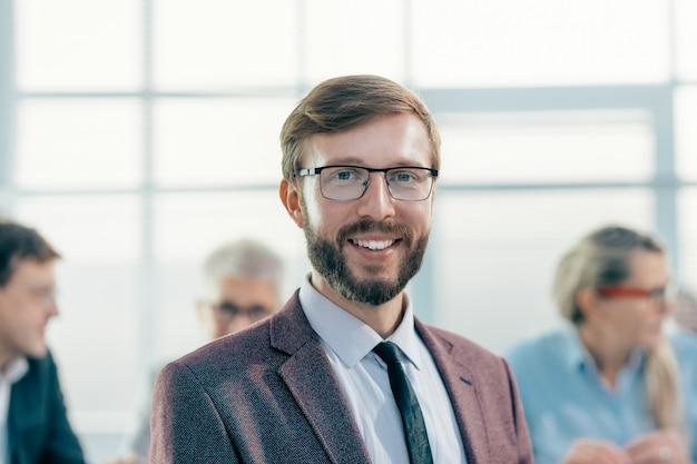 閉じる。オフィスに立っている笑顔のビジネスマン。社会人