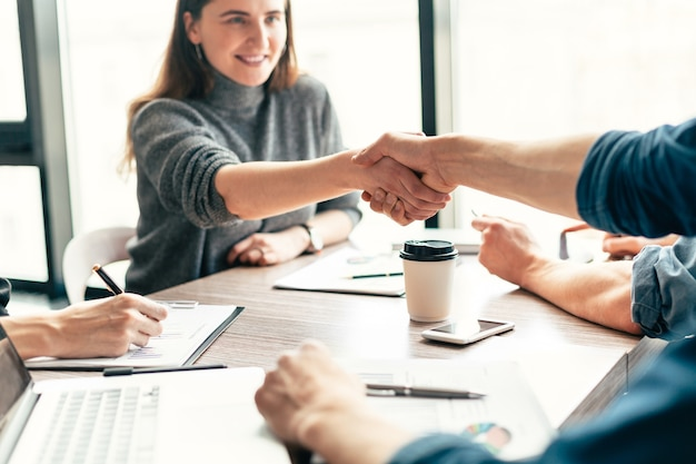 同僚と握手する笑顔のビジネスウーマンを閉じる