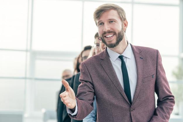 閉じる。握手のために彼の手を差し出して笑顔の実業家。社会人