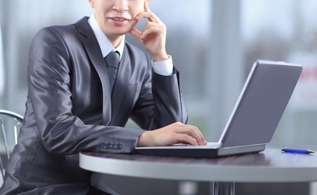 Крупным планом. улыбающийся бизнесмен, сидя перед открытым ноутбуком