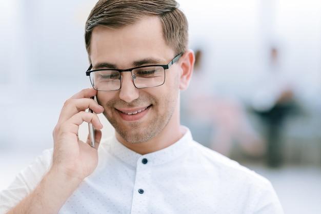 クローズアップ。彼のスマートフォンで話している笑顔のビジネスマン。ビジネスコンセプト