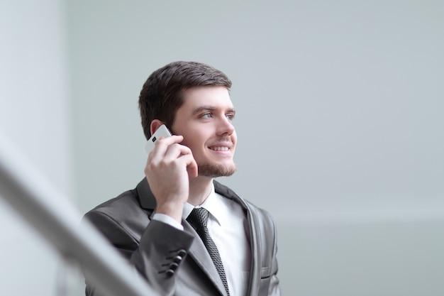 Закройте вверх. улыбающийся бизнесмен разговаривает на смартфоне в офисе.