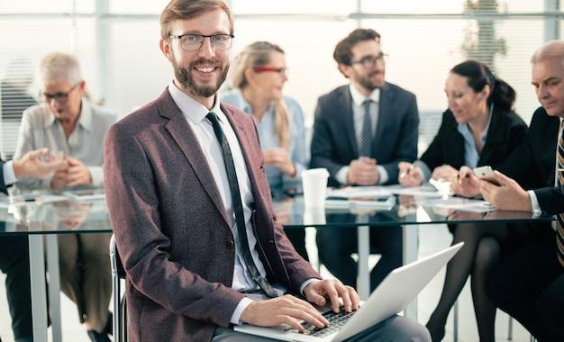 閉じる。オフィスでラップトップを使用して笑顔のビジネスマン