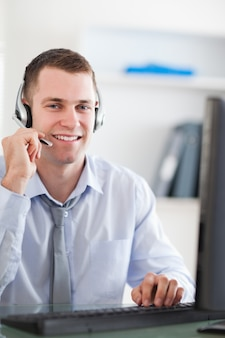 Close up of smiling call center agent speaking with costumer