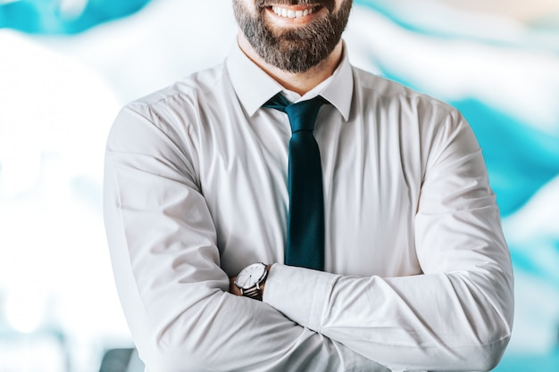 Close up of smiling caucasian businessman standing with arms crossed.