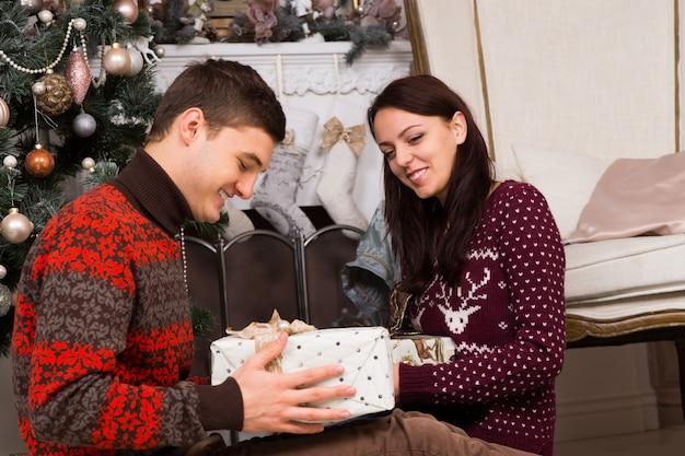 クリスマスツリーと飾られた煙突の壁の近くにプレゼントボックスを保持しているトレンディな冬の服装で笑顔のカップルを閉じる