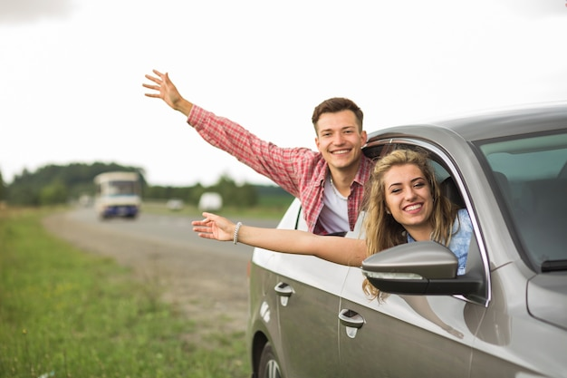Close-up of smiling couple waving hands out from car window