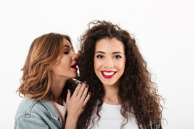 Close up smiling curly girl looking at the camera while her friend talking her in ear over white wall