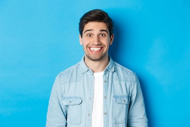 Primo piano di un uomo eccitato sorridente con la barba, che guarda divertito la pubblicità, in piedi su sfondo blu