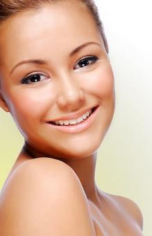 Крупным планом улыбающееся лицо молодой взрослой красивой женщины