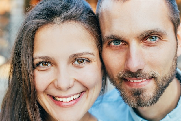 Close-up on smiling faces of young woman and man