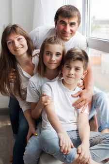 Close-up of smiling family sitting on window sill at home