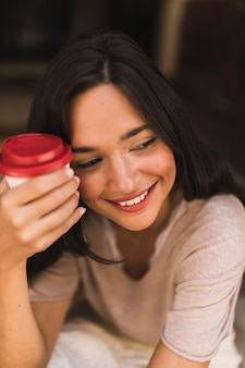 Close-up of a smiling girl holding takeaway coffee cup