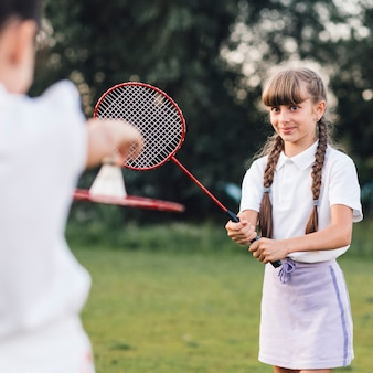Close-up of a smiling girl playing badminton with her friend