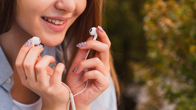 Close-up smiling girl taking out headphones