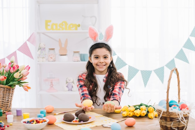 Close-up of a smiling girl wearing bunny ears showing colorful easter eggs