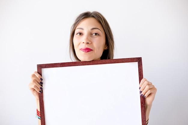 Макро улыбается девушка с пустым белым плакатом или плакатом