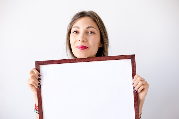 Close-up smiling girl with a blank white placard or poster