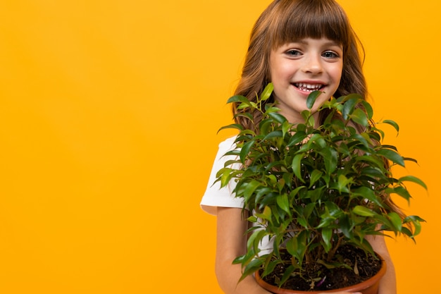 Close-up of a smiling girl with a flower in a pot on orange isolated
