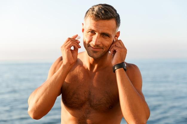 Close up of smiling handsome shirtless sportsman