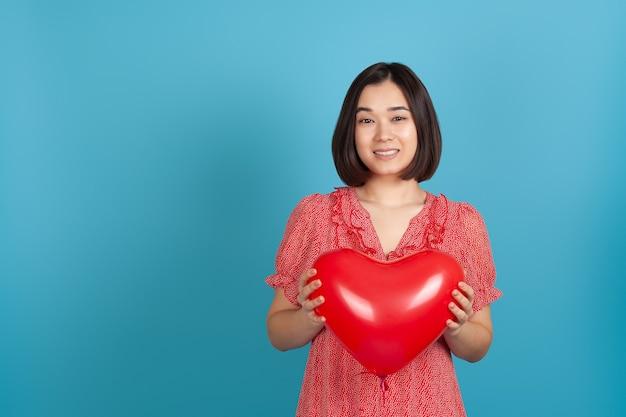 Крупным планом улыбается счастливая азиатская женщина, держащая красный воздушный шар в форме сердца