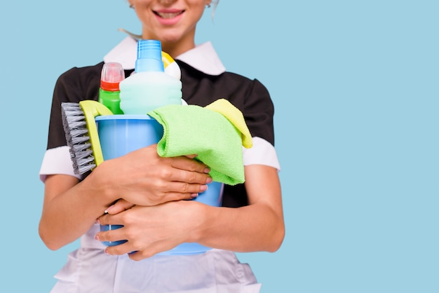 Close-up of smiling housekeeper holding bucket with cleaning equipment against blue background