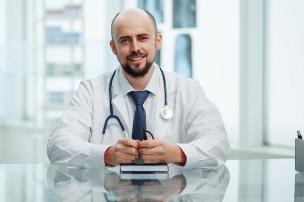 확대. 그의 책상에 앉아 당신을 찾고 웃는 남성 의사.