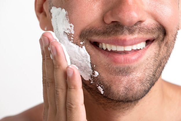 Close-up of smiling man applying shaving foam